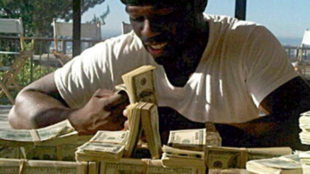 50-cent-sitting-with-money-stacks.jpg