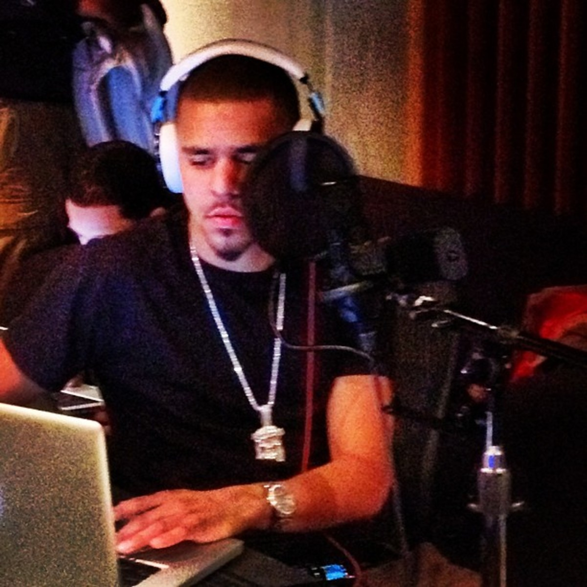 J. Cole recording in the studio, young